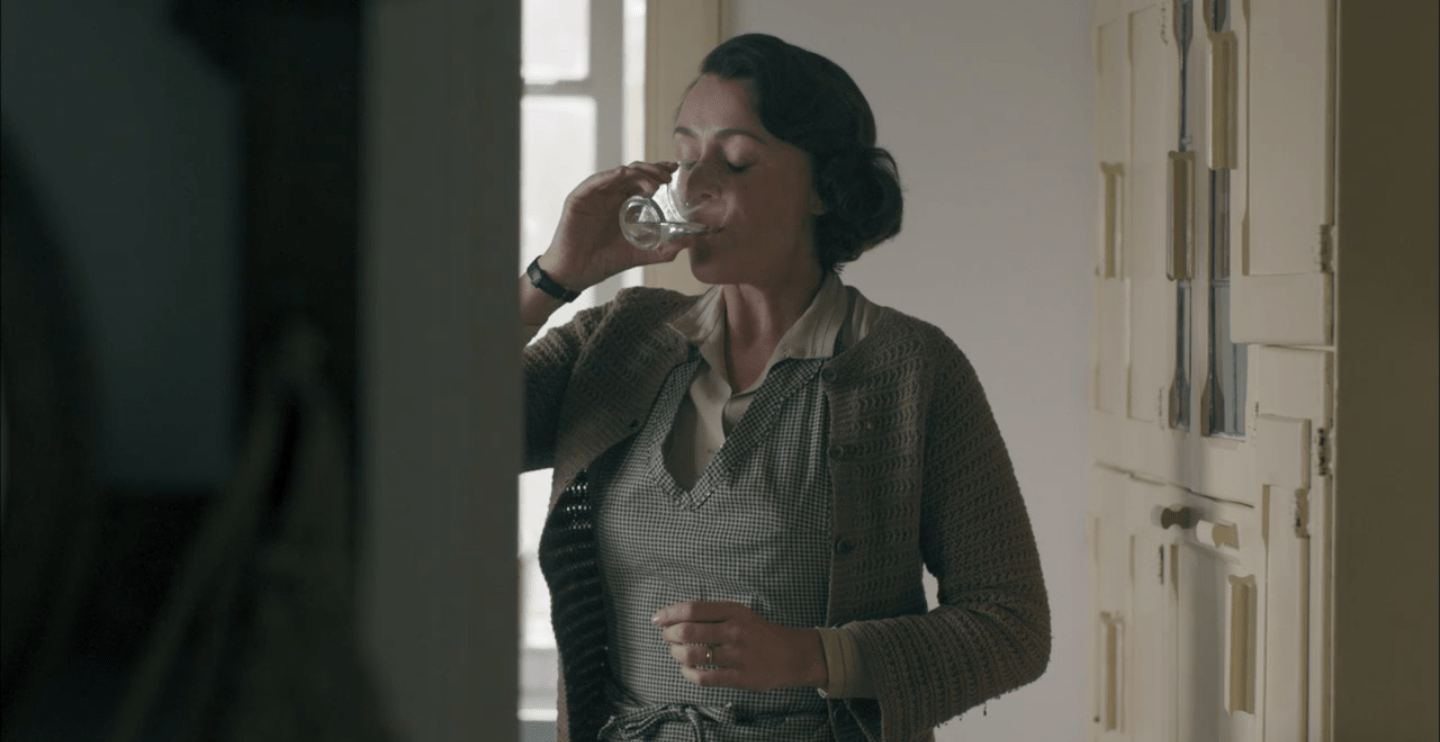 Louisa drinking gin from a clear glass.