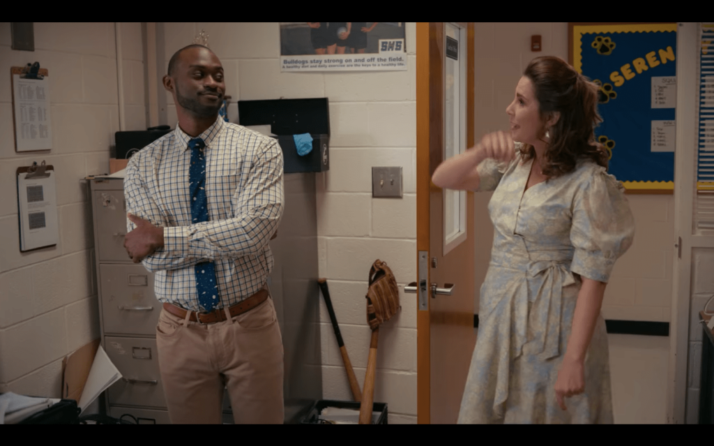 White woman in a floral dress with puffy sleeves, speaking to a Black man who looks very skeptical.