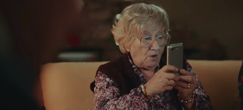 Older woman wearing glasses holding up a smartphone in front of her.