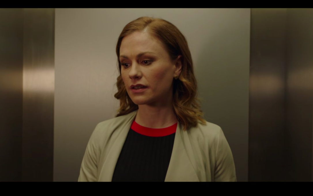 Robyn in an elevator looking sad.