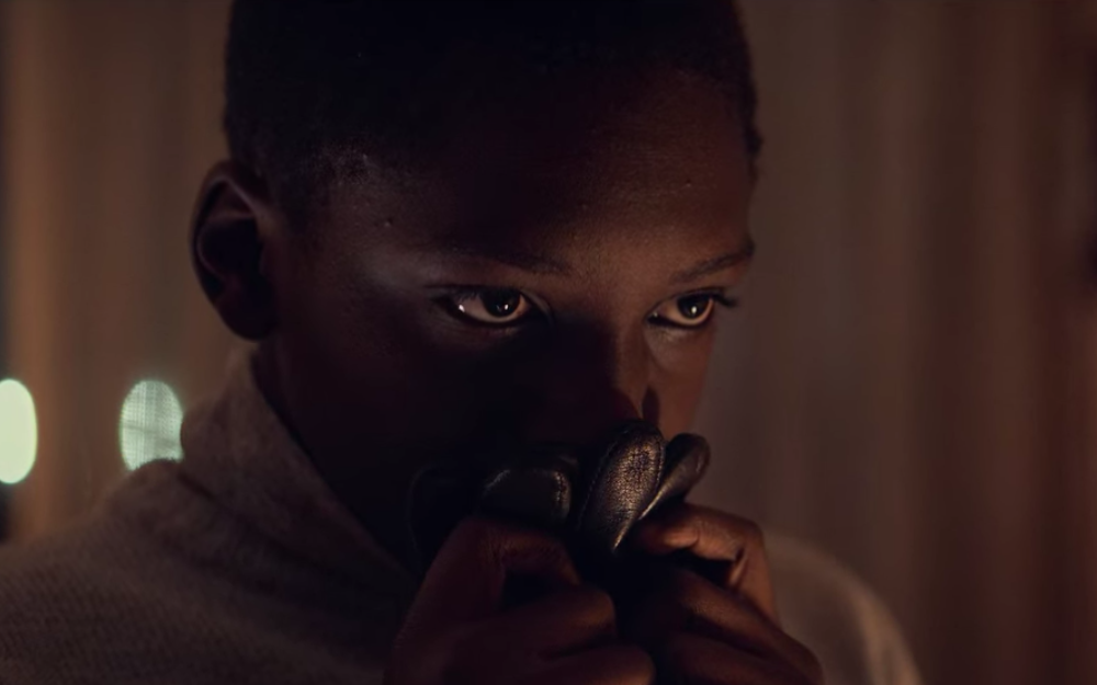A close up of young Assane's face as he holds a pair of his father's black gloves to his nose.