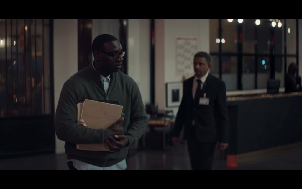 Assane disguised as a courier. He is wearing a green sweater over a button down shirt. He has on glasses and carries manilla folders. His body is hunched forward and he looks nervous. Behind him is a security guard who is walking toward him.