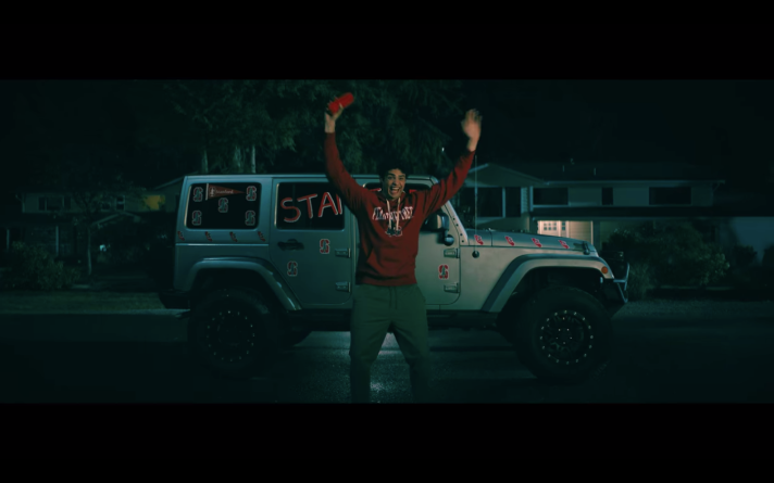 Peter standing in front of his Jeep that has been covered with Stanford-themed decoration. He is wearing a Stanford sweatshirt and his arms are raised in excitement.