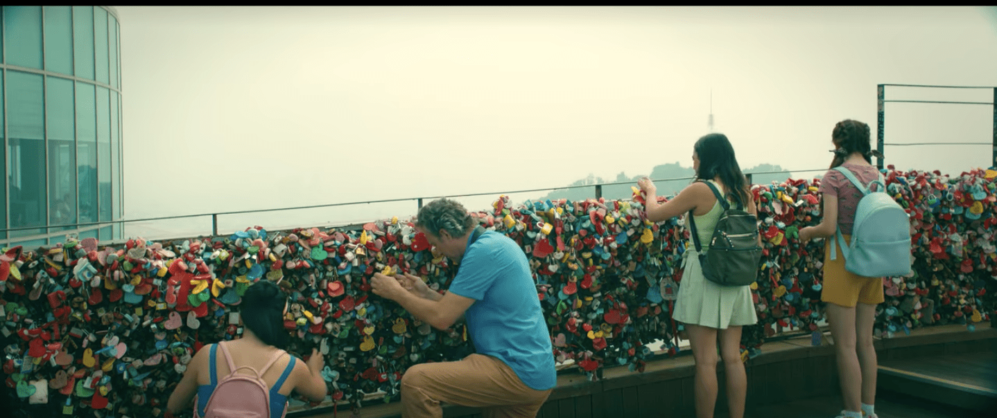 Image of four people standing at low fence that is covered in brightly colored padlocks.