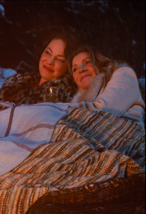 Middle-aged Tully and Kate sit together outside under blankets. Their heads are leaned together and a glass of champagne is visible.