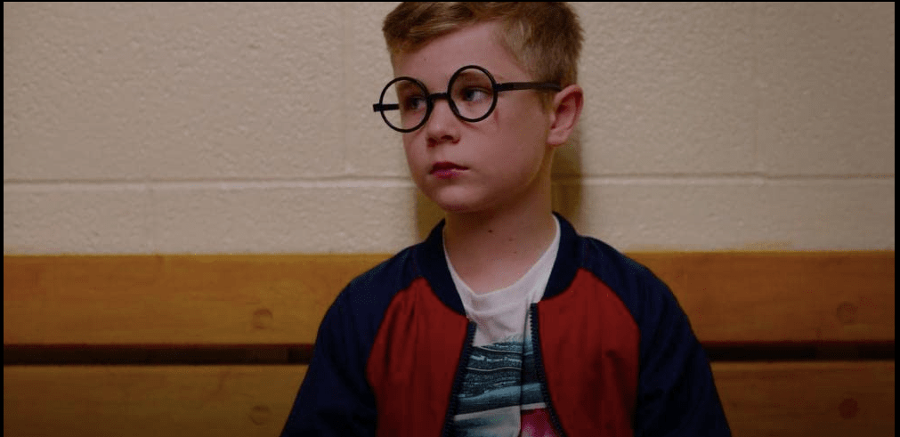 White boy with short blonde hair and black plastic Harry Potter-style glasses looking to one side. He is wearing a red and blue jacket over a white and blue tee-shirt.