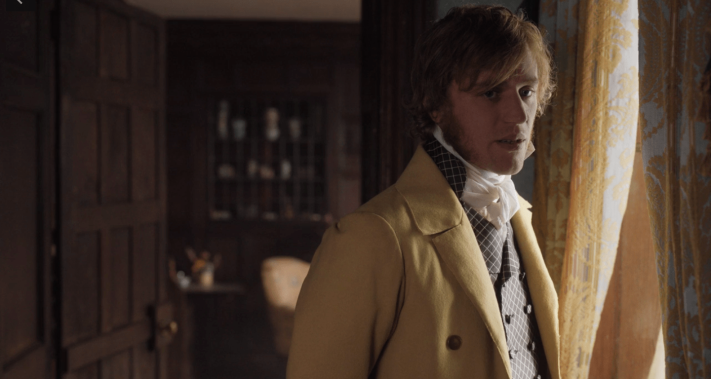 Mr. Knightley, dressed in a yellow coat, patterned vest, and a shirt with a high, white collar stands near a window that is draped with blue and yellow/gold curtains.