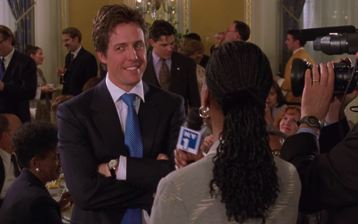 Hugh Grant, wearing a suit and blue tie, looking to one side while he gives an interview to a reporter and a cameraman. Behind him are people attending a large fundraising gala.