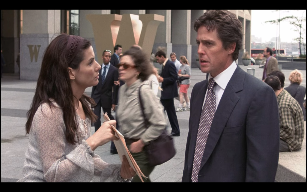 Sandra Bullock, wearing a loose fitting shirt and cloth headband, holds papers that she's showing to Hugh Grant, so is in a suit and tie. They are standing outside a building with a large letter W in front of it and people milling about.