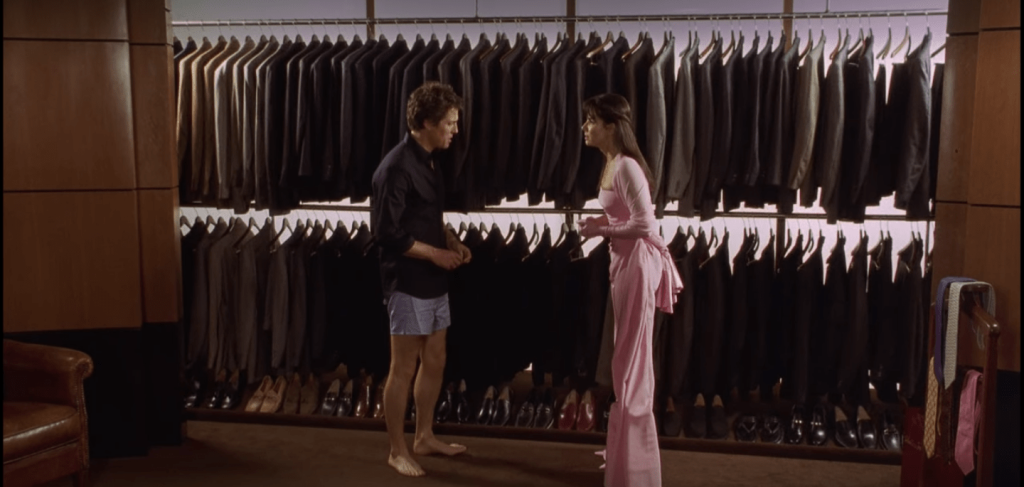 Hugh Grant, wearing a button down shirt and light blue boxers, stands next to Sandra Bullock, who is wearing a long pink bridesmaid gown. Behind them are two rows of suits on hangers with hundreds of pairs of shoes neatly arranged below them.