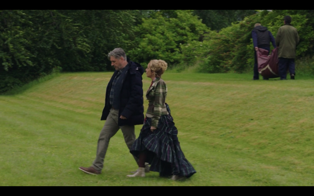 Howard and Annabelle walking across a mowed lawn. He is wearing a button down shirt, pants, a jacket, and brown shoes. She is wearing a plaid jacket with puffed sleeves and peplum, a plaid ruffled skirt that is knee-length in the front and ankle-length in the back, and a pair of plaid high-top sneakers.