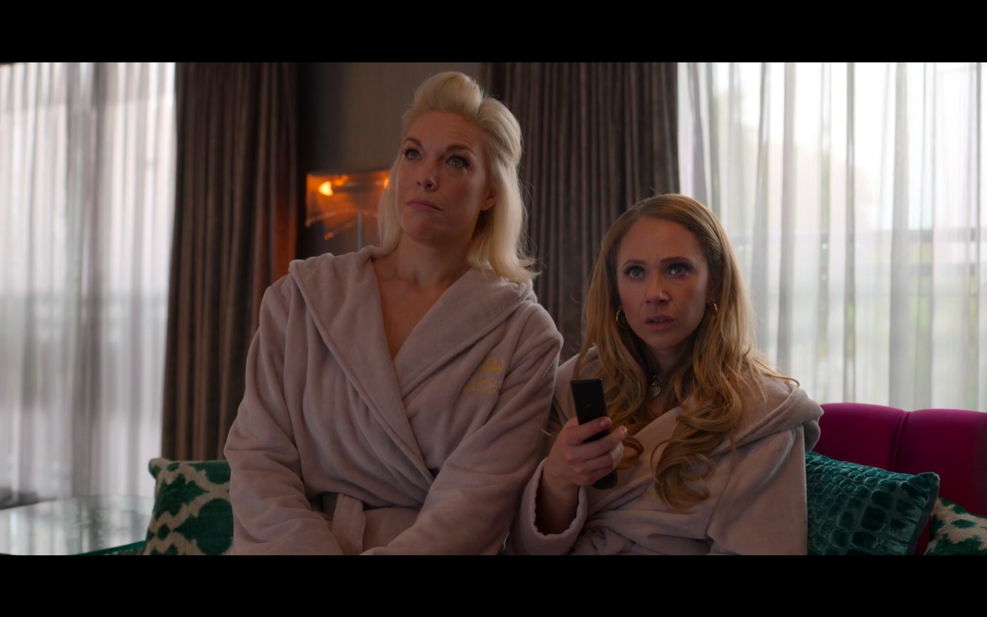 Rebecca and Keeley sit on a couch in a hotel wearing matching beige bathrobes. They are looking