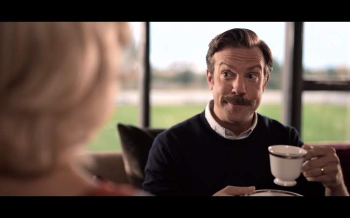 Ted Lasso holding a tea cup and looking at Rebecca with a quizzical look on his face.