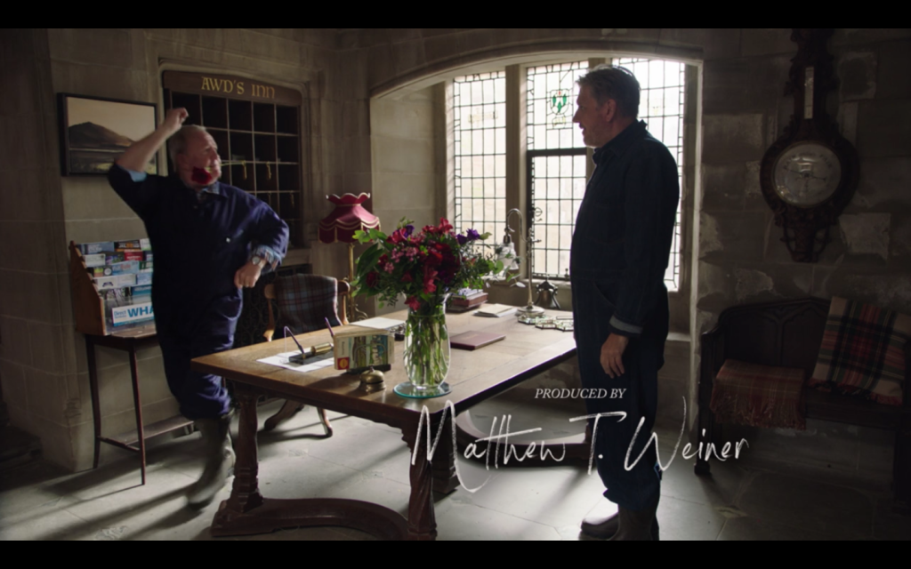 Gavin and Howard, both wearing blue coveralls, standing at the reception area of the inn. Gavin is dancing with a flower clenched between his teeth and Howard is watching him.