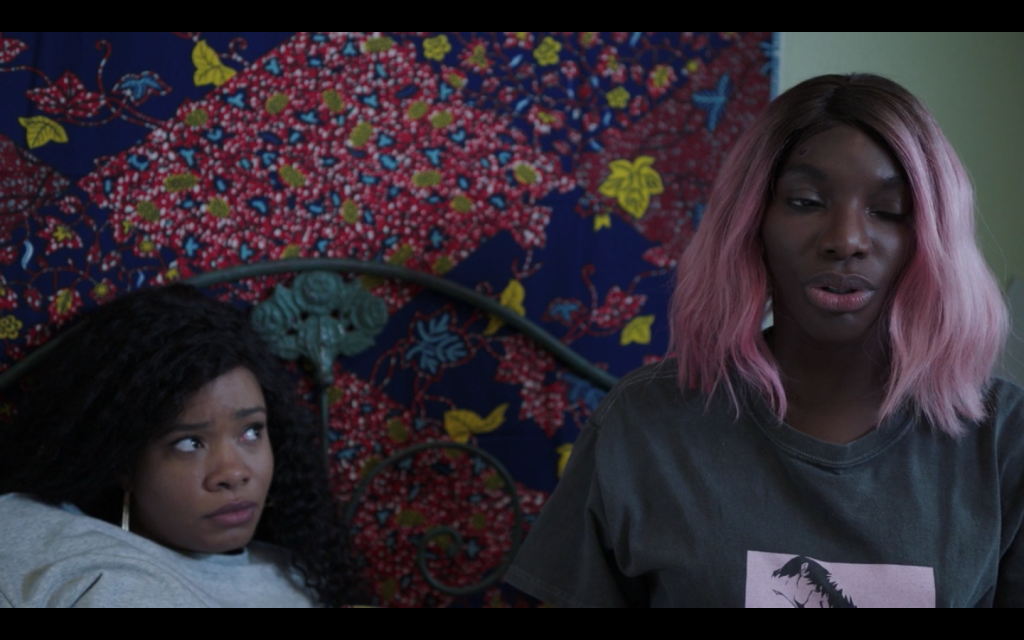 Terry, a Black woman with long curly hair, leans against Arabella's green iron headboard. She is looking with concern at Arabella, who sits next to her. Behind them is a colorful tapestry with leaves and flowers in blues, pinks, and yellows.