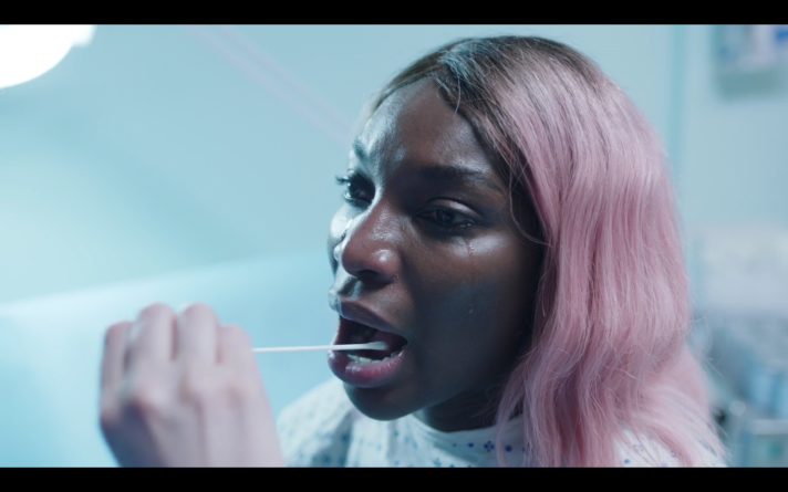 Arabella, a Black woman wearing a pink wig and a hospital gown, with her mouth open as a swab, held in a white person's hand, goes into her mouth. There is a tear running down her cheek and she looks distraught.