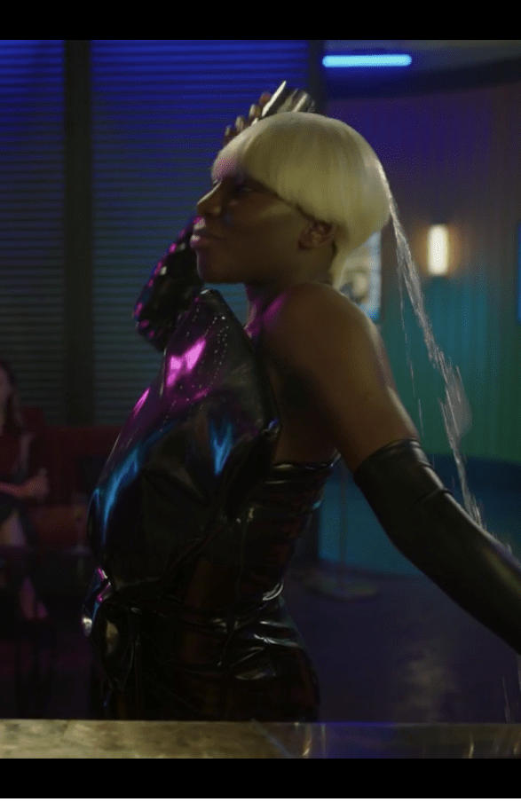 Arabella wearing a black leather dress with a huge bow in front, above the elbow gloves, and a platinum blonde bowl cut wig, throws part of her drink over her shoulder.