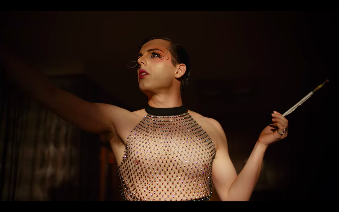 Austin in a costume. He is wearing a chain mail kind of top that is sleeveless and has a velvet choker collar. He has extremely long false eyelashes and is holding a long cigarette holder.