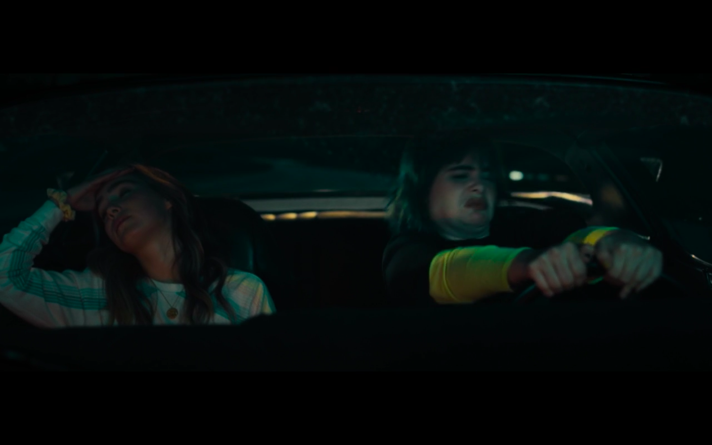 Bailey driving while making a disgusted expression. Veronica has her head leaned back and her hand on her forehead.