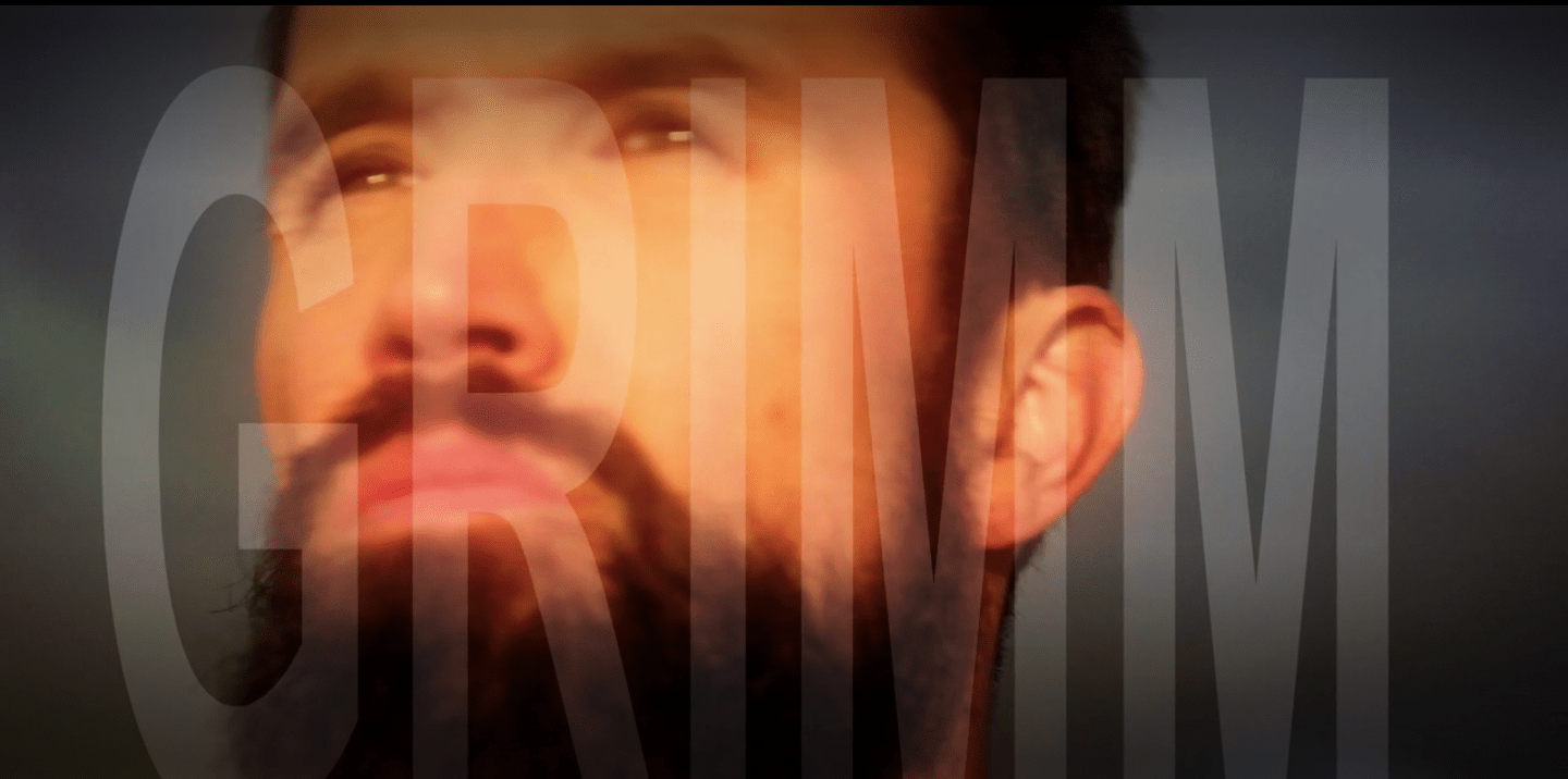 Ian's face--a white man with short dark hair, brown eyes and a dark, bushy beard--looking pensively into the distance. The name Grimm is superimposed over his face in large, white letters.