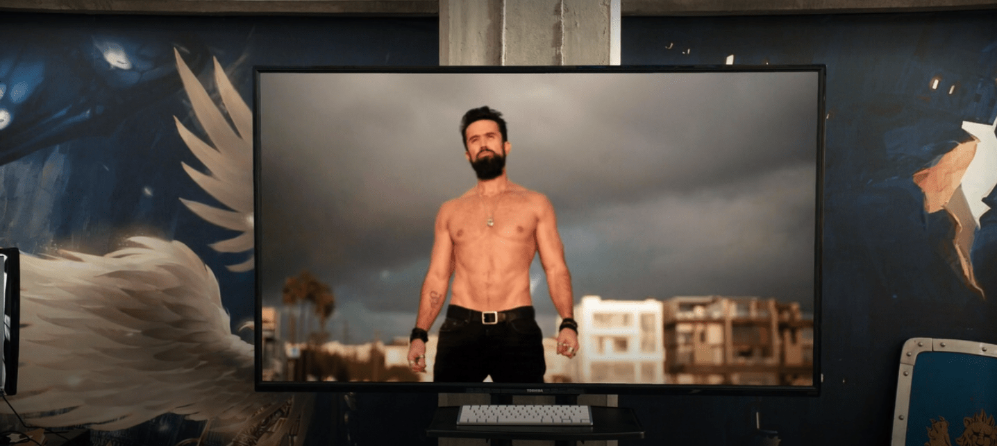 A television screen showing Ian standing shirtless on a beach with storm clouds behind him. His hands are at his sides, his hands lightly clenched. He has several black bracelets on each wrist. He's wearing black pants and a black belt.