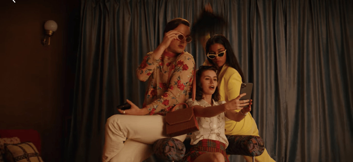 Austin, Penny, and Mia are posing for selfies in their living room. Austin and Mia are wearing sunglasses. Austin has on a floral blouse and white pants and purse over his shoulder. Mia is wearing a yellow suit and holds some peacock feather above her head. Penny is wearing a white shirt and is seated on a chair. She holds her phone out at arm's length while they all pose.