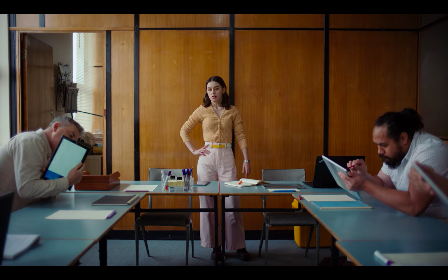 Penny standing in a conference room with a hand on her hip as a several men clumsily attempt to use tablets.