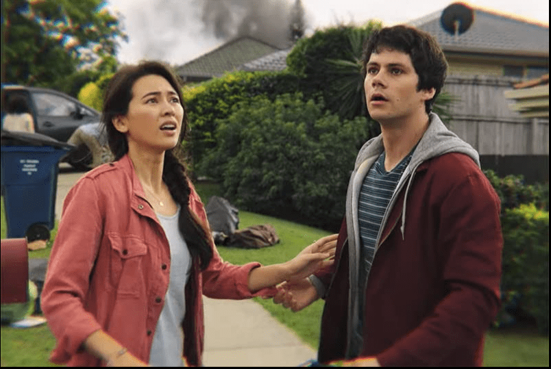Aimee who has long brown hair and is wearing a pink button down shirt over a tank top, and Joel, sho has short brown hair and is wearing a maroon sweatshirt over a striped shirt, are looking into the distance with scared expressions on their faces. Their hands are reaching for each other.