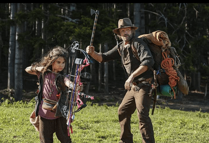 Minnow, who is holding a loaded crossbow with pink arrows, stands next to Clyde who has a small axe raised in one hand and wears a brown hat and carries a lot of gear on his back.