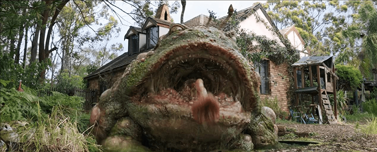 A giant frog sits beside a half-ruined house. The frog reaches the second floor windows and its tongue is extended out toward the viewer.