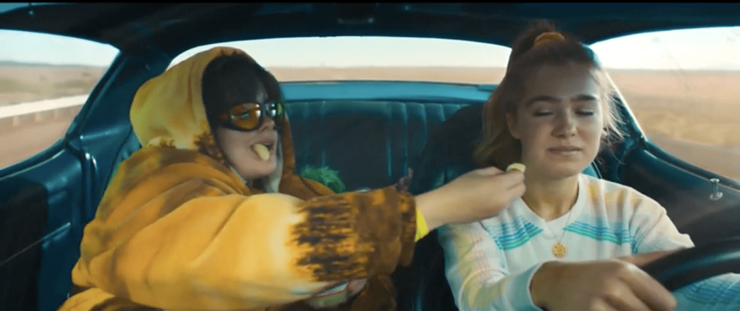 Bailey, wearing a large, yellow sweatshirt, offering Veronica a pickled pear while she drives. Veronica looks unimpressed.