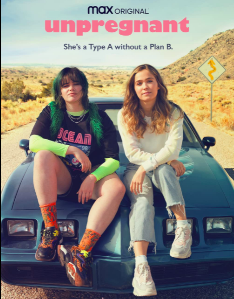 Blonde teenage girl wearing a white shirt, light wash jeans, and white sneakers sitting next to a black and green haired girl wearing a black graphic tee-shirt over a neon green shirt, shorts, orange socks, and orange and black sneakers. They are sitting on a blue trans am in the middle of a road running through the desert.