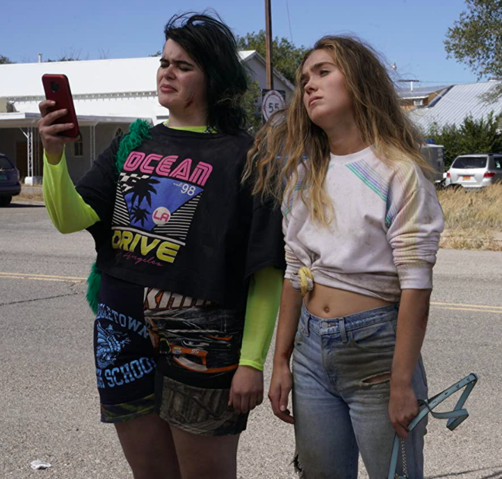 Bailey and Veronica, covered in dirt and their hair a mess, standing near a road. Veronica looks exhausted and sad. Bailey is looking at her phone with a confused expression.