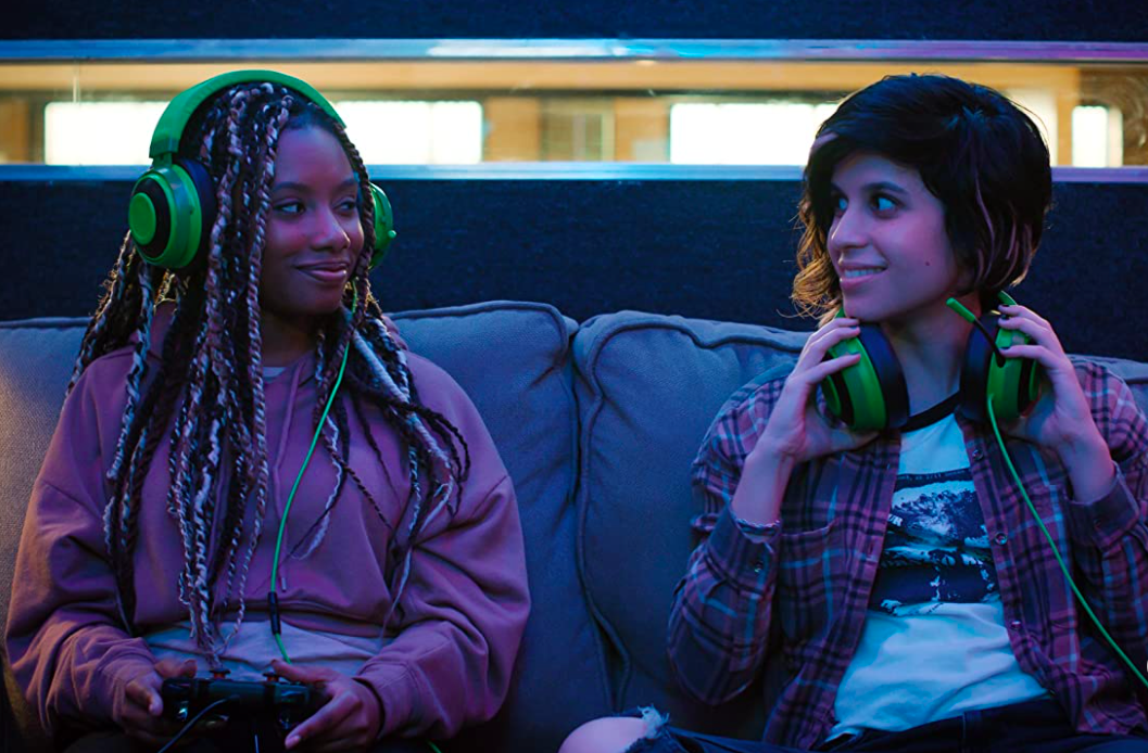 Dana, a black woman with long twists, and Rachel a white woman with chin length hair, sit next to each other in the testing booth. They both have large green headphones.