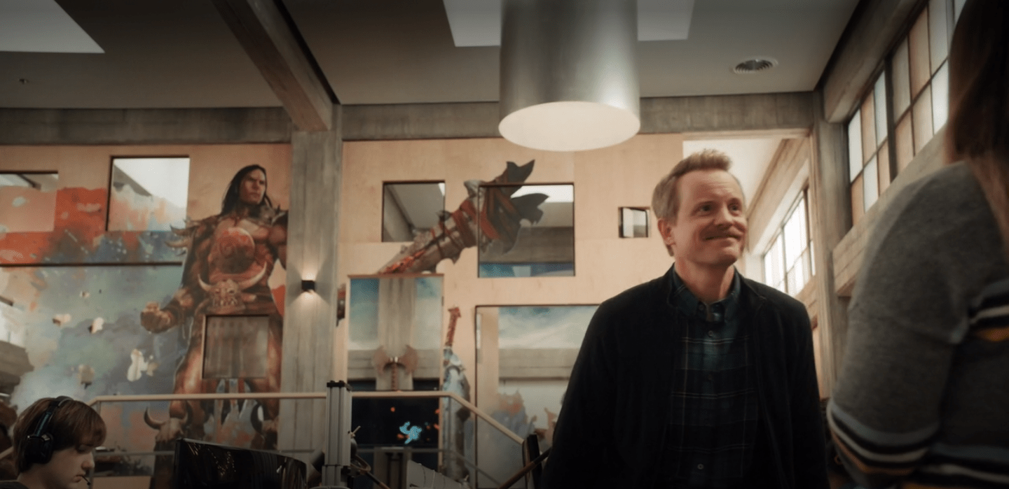 David--a white man with short strawberry blonde hair and a mustache--sits on a desk. In the background we can see the outside of Ian's office, which is decorate with the image of a man in gladiator clothing. There is a window directly over where his crotch would be.