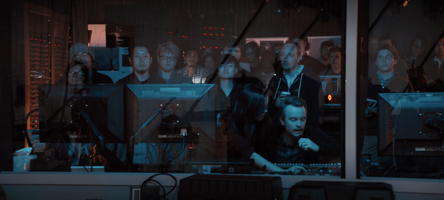 Large group of very bored looking employees standing in a control booth as David leans forward to speak into a microphone.