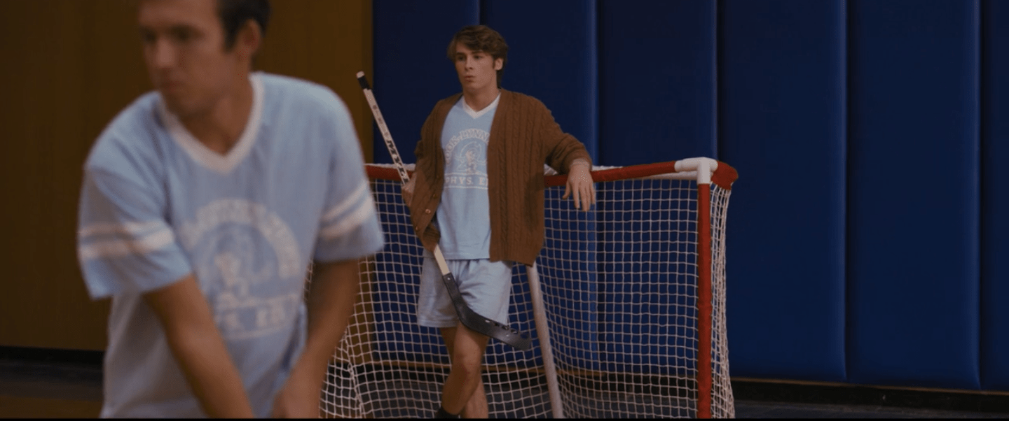 Hunter, a white teenage boy with floppy brown hair, leans against a red floor hockey goal. He is wearing a light blue uniform with a brown cardigan sweater over it. He is holding a hockey stick and looks very relaxed.