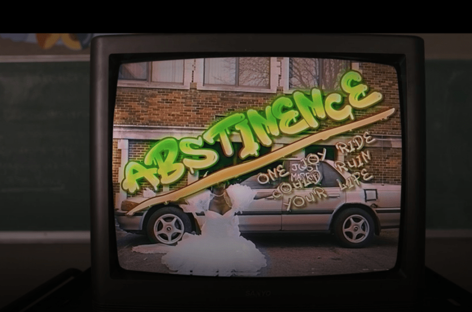 An old TV sits on a stand in a classroom. The image on the TV screen shows a beat up car in front of a brick building. In front of the car is a Black woman wearing a wedding dress kneeling with her arms outstretched. Superimposed over the image, in writing meant to emulate graffiti, are the words: Abstinence: One joy ride could ruin your life.