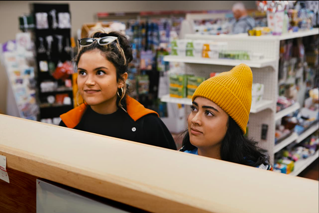 Lupe and Sunny standing at the very tall pharmacy counter as they speak to the pharamacist.