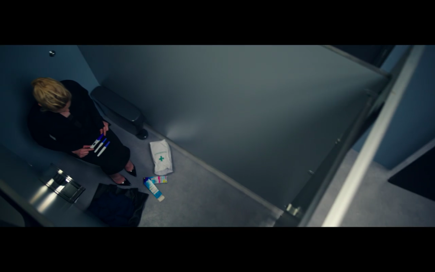 Robyn in a bathroom stall seated on the toilet with several pregnancy tests lined up on her lap and many empty boxes on the floor around her at her feet.