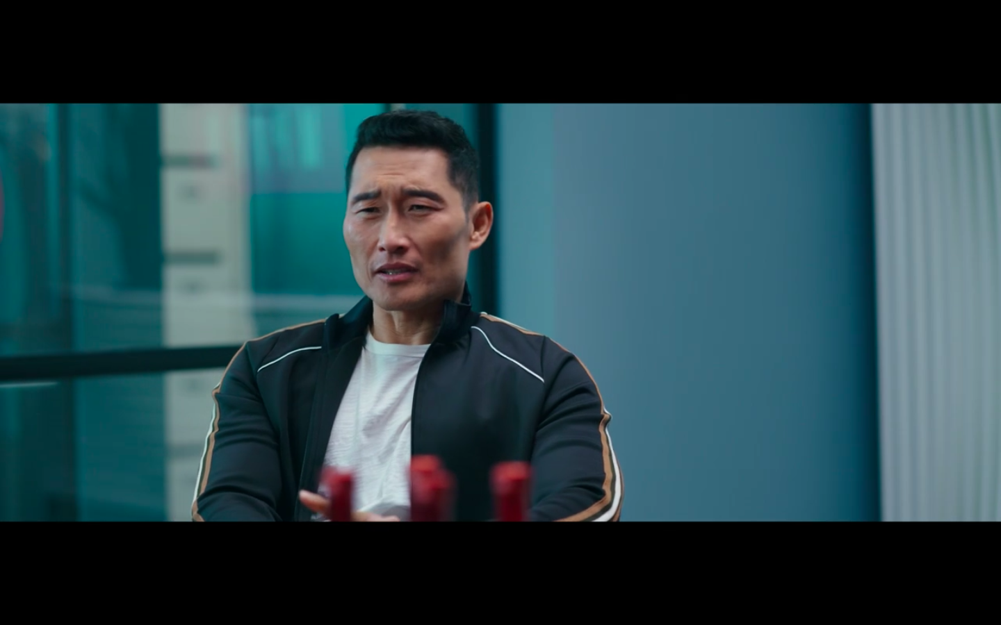 Close up of Daniel Dae Kim who is wearing a white shirt and black warm up jacket.