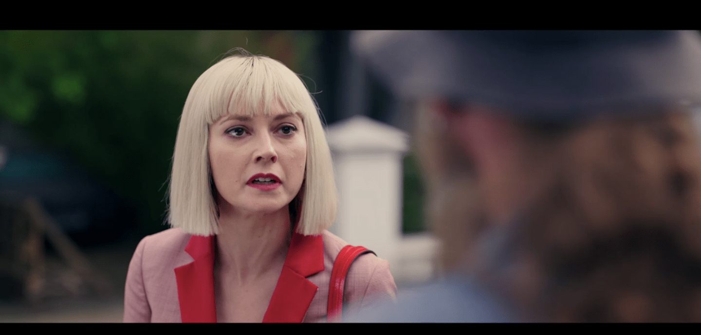 Eve, wearing a pink and red suit, leaning forward to tell off a man with a long ponytail, a hat, and a beard outside an abortion clinic.
