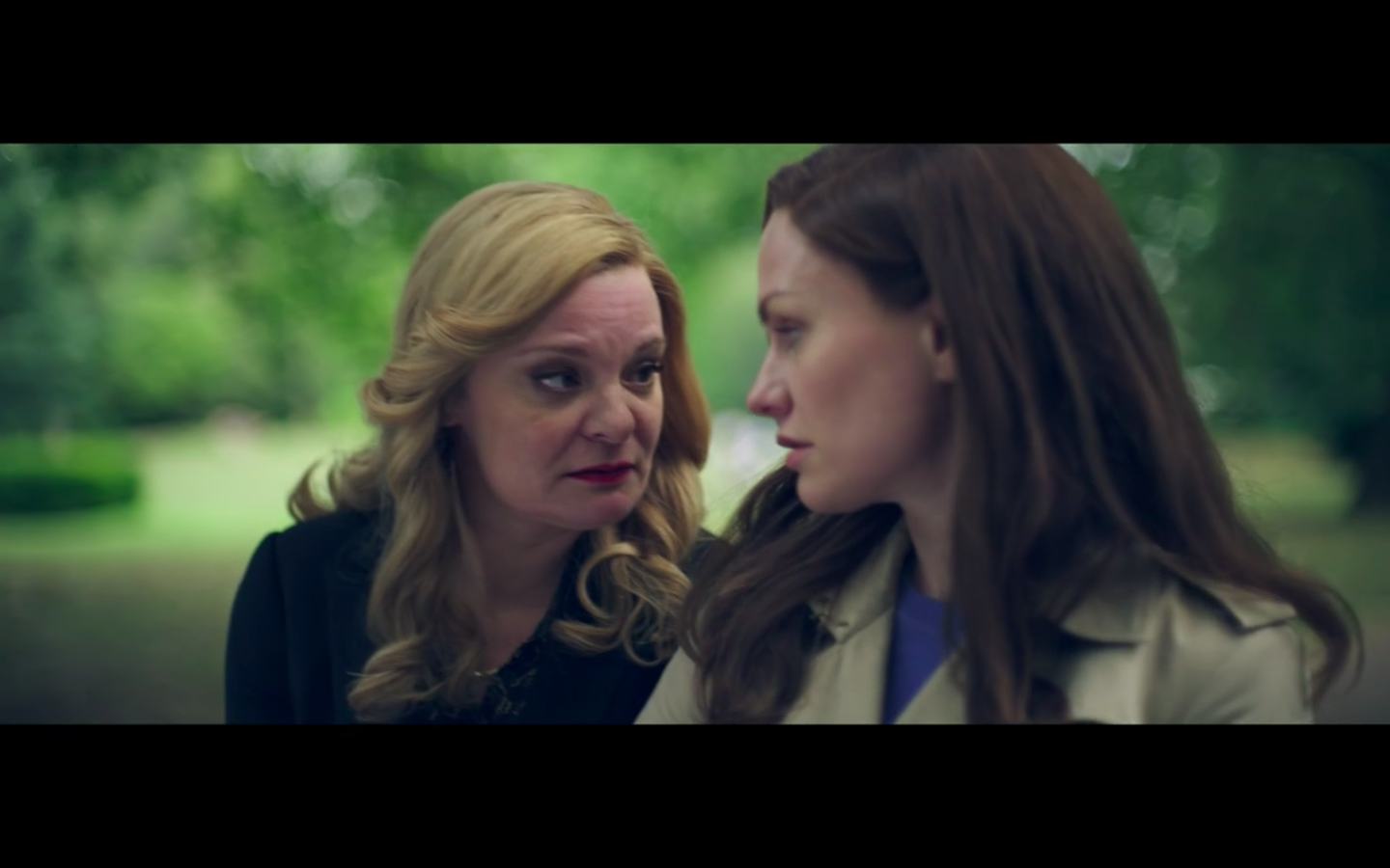 Martha Plimpton as Robyn's mother. She has long blonde hair and Robyn has long dark hair. They are both wearing trench coats as they walk through a park. They are looking at each other.