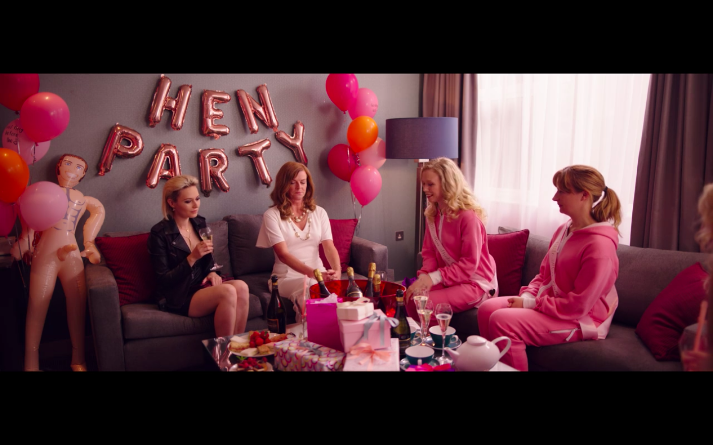 Eve, wearing a low-cut black dress, a black leather jacket, and black eye makeup with her hair slicked back sits next to her mother who is wearing a white dress. Behind them are balloon letters spelling out HEN PARTY. On either side of them are balloons. Next to Eve is a male sex doll. Other guests are dressed in vibrant pink warm up suits with pink sashes. The gifts are all wrapped in pink.