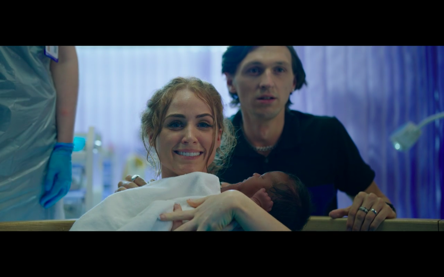 A white woman who has just given birth holds a supposedly new born Black baby while her shell-shocked white husband looks on from behind her.