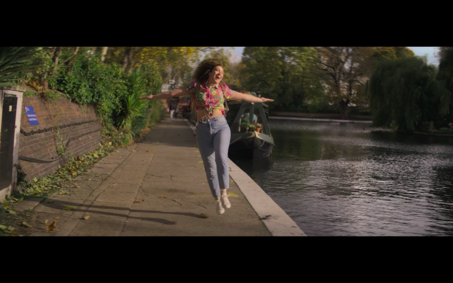 Jessie in light wash high-waisted, tapered jeans, white sneakers, and a floral top tied above her navel, leaping with her arms spread wide and her mouth open in joy as she leaves a boat house docked in a canal.