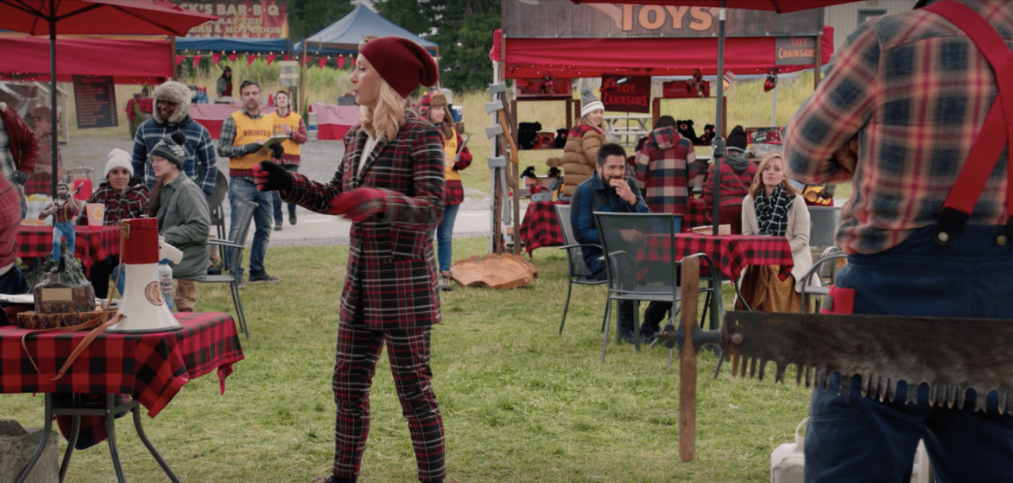 Muriel at the Lumberjack Festival where there is a LOT of plaid. Muriel is wearing a red and black plaid suit with a red hat and black high heeled work boots.