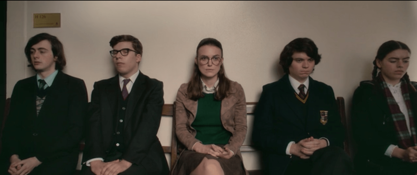 Sally, wearing large glasses, a tan jacket and green sweater, sits between mostly young men and one younger woman, waiting her turn to be interviewd.