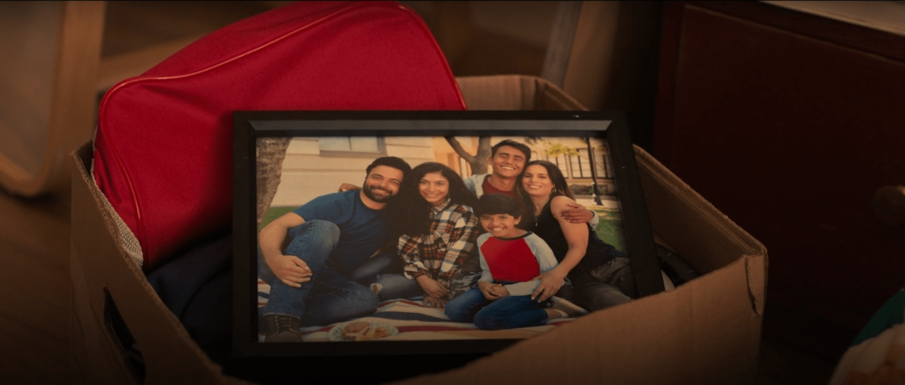 Photograph of Victor's family (Father, mother, brother, and sister)resting on top of a cardboard box.