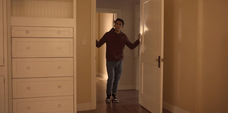 Victor stands in the doorway to his new empty bedroom.